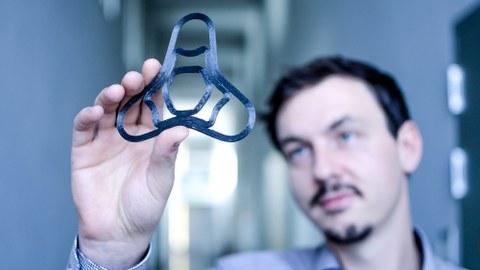 ILK-Wissenschaftler Andreas Borowski prüft ein generativ gefertigtes endlosfaserverstärktes CF-PEEK-Bauteil