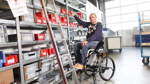 Ein Mann sitzt im Rollstuhl und greift nach einer Ware im Regal.