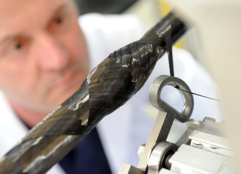 Ein Mitarbeiter des Instituts für Leichtbau und Kunststofftechnik der TU Dresden blickt auf eine laufende Wickelmaschine.