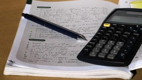 Geööfnetes Mathebuch mit darin liegendem Stift und Taschenrechner