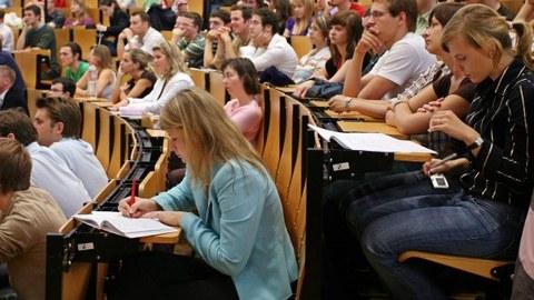 Hörsaal mit Studenten, Im Vordergrund Studentin mit offenem Buch, schreibend, Prüfung