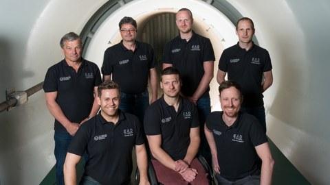 Gruppenbild Mitarbeiter Arbeitsgruppe Experimentelle Aerodynamik, Bild zeigt sieben Mitareiter der Arbeitsgruppe im Windkanal. Im Hintergrund ist der Kollektor des Niedergeschwindigkeitswindkanals zu erkennen.