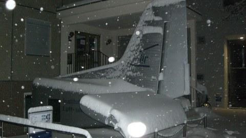 schneebedecktes Heck einer Do228 vor dem Institutsgebäude