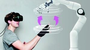 ein potentieller Anwender (trägt VR Brille) interagiert mit einem Industrieroboter