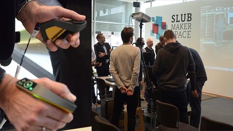 links: Nutzung eines neuartigen Eingabemediums zur Steuerung von Baumaschinen; rechts: Zuschauer verfolgen auf einer Beamerwand, wie die Eingaben im neuen Steuergerät in einer Simulation umgesetzt werden