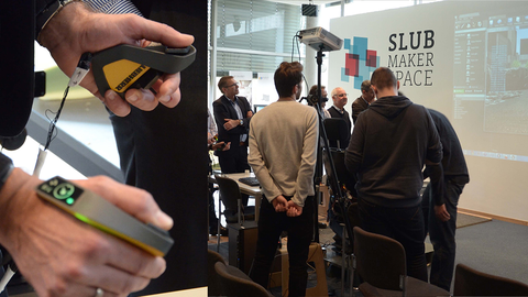 left: a new innovative input method for controlling construction vehicles; right: a crowd of people watching on a presenter-screen how the new method works on vehicles in a simulated environment