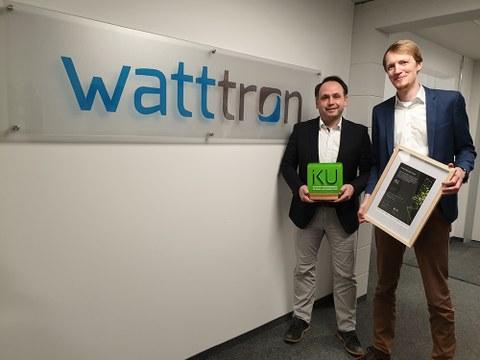 """Marcus Stein und Sascha Bach vor Schild mit der Aufschrift """"watttron""""."""