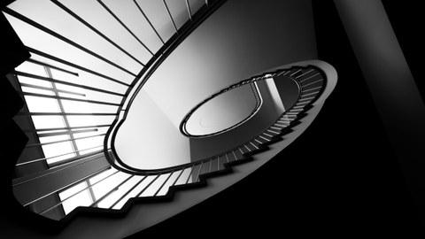 Treppe im Andreas-Schubert-Bau. Das Foto wurde vom Boden aus aufgenommen und ist in schwarz-weiß. Aus dieser Perspektive verläuft die Treppe spiralförmig nach oben.