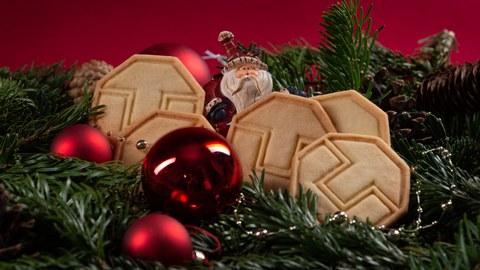 Foto von einem rotgeschmückten Adventskranz, mit Weihnachtsmann, Tannenzapfen und 5 Keksen.