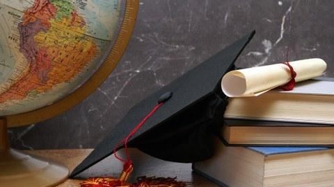 Das Foto zeigt einen verschiedene Gegenstände, die nebeneinander auf einem Tisch liegen. Unter anderem erkennt man einen Globus, einen Doktorhut, ein Diplom und mehrere Bücher.