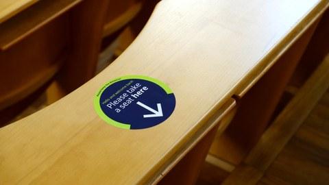 """Foto eines Hörsaals mit Hinweisaufkleber an einem Sitzplatz mit der Aufschrift """"Please take a seat here.""""."""