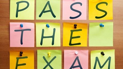 """Auf dem Bild sind bunte Notizzettel auf einem Hintergrund aus Holz angeordnet. Jeder Zettel ist mit einem Großbuchstaben beschriftet. Zusammen ergeben sie die Wörter """"Pass the exam""""."""