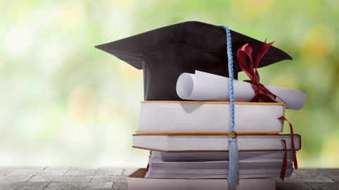The photo shows a small stack of books. On top of it stands a doctoral hat. A diploma is beside it.