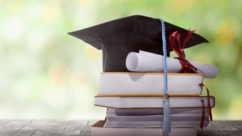 Das Foto zeigt einen kleinen Bücherstapel. Auf diesem steht ein Doktorhut. Ein Diplom liegt daneben.