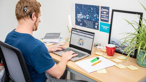 Foto eines Studierenden mit Hörgerät. Er sitzt an einem Schreibtisch vor seinem Notebook.