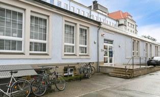 Das Foto zeigt den Eingang von Haus D in Dobritz, man sieht davor Fahrräder.