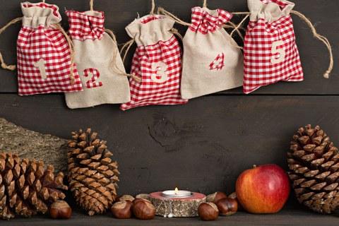 Foto von 5 hängenden Weihnachtsbeuteln, einer leuchtenden Kerze mit Kastanien, einem Apfel und Tannenzapfen