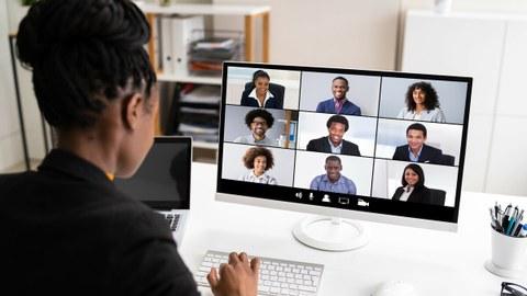 Das Foto zeigt eine Frau an ihrem Schreibtisch. Sie nimmt gerade an einer Videokonferenz teil.