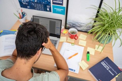 Das Foto zeigt einen Studenten an seinem Schreibtisch. Vor ihm steht sein Laptop und viele weitere Büromaterialien. Mit den Händen stützt er seinen Kopf ab.