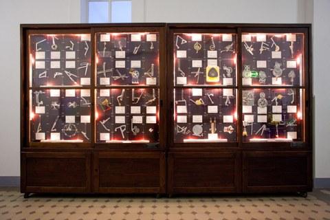 Foto: ein historischer Ausstellungsschrank mit mehreren Modellen von Getrieben. Die Fakultät Maschinenwesen hat mehrere dieser Ausstellungsschränke, wobei die Modelle alle beweglich sind, weshalb diese Schränke auch als Zappelschränke bezeichnet werden.