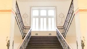 Foto: repräsentatives Haupttreppenhaus des Zeuner-Baus, des Hauptgebäudes der Fakultät Maschinenwesen. Blick von unten, auf das Halbpodest mit großem Fenster. Das Treppenhaus ist ausgestattet mit historischer Malerei und schmiedeeisernem Geländer.
