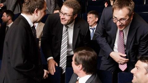 Foto: mehrere Professoren die sich in verschiedenen Gesprächen angeregt miteinander unterhalten