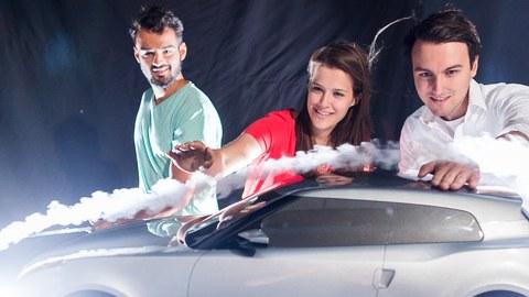 Foto: 3 Studierende blicken begeistert auf ein Modellauto, das von einer sichtbaren Luftströmung umflossen wird.