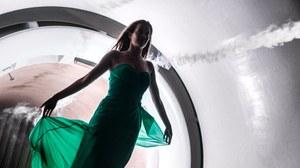 Foto: Eine junge Frau im grünen Abendkleid steht vor einem Windkanal und ein schmaler weißer Luftstrahl aus dieser Anlage streift sie und umfließt sie