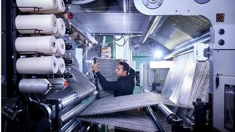 Foto: Eine komplexe Webmaschine, links befinden sich verschiedene Rollen Garn, von denen laufen über verschiedene Rollen sehr viele Fäden parallel, die von der Maschine zu einem Stoff verwebt werden. Hinter der Maschine prüft eine Person den Stoff.