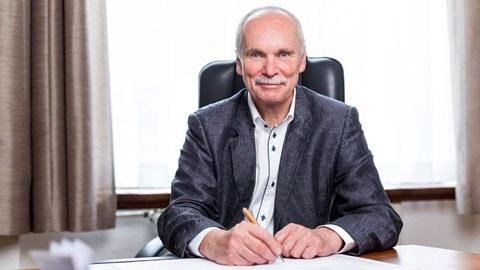 Portraitfoto von Professor Stelzer, Inhaber der Professur für Konstruktionstechnik/CAD. Er sitzt an einem Schreibtisch und blickt neugierig in Richtung des Betrachters.