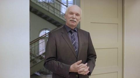 Foto: Der Dekan der Fakultät, Prof. Stelzer steht in einer Tür und spricht in Richtung der Kamera. Im Hintergrund ist ein Treppenhaus zu sehen.