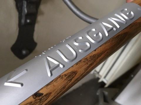 Foto: Detailaufnahme eines Handlaufschildes aus Aluminium, auf dem das Wort Ausgang in Braille und erhabener Pyramidenschrift und ein Pfeil zu sehen ist.