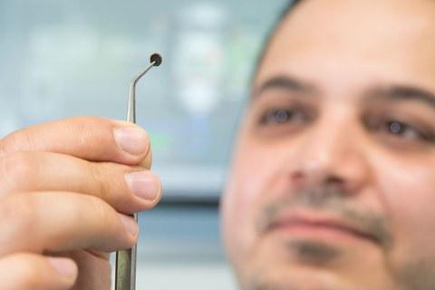 Foto: Der Nachwuchswissenschaftler Muhannad Al Aiti zeigt ein kleines Stück aufbereitetes Lignin mit einer Pinzette.