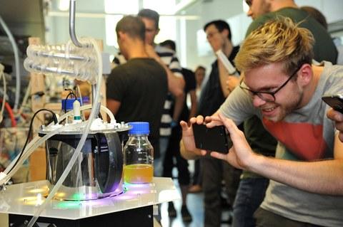 Foto: Ein Student fotografiert während einer Ausstellung mit seinem Handy den Bioreaktor der TU-dresden, er blickt begeistert