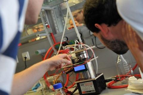 Foto: Zwei Studenten stehen vor dem kleinen Bioreaktor des Studierenden-Teams der Universität Stuttgart und betrachten ihn genau.