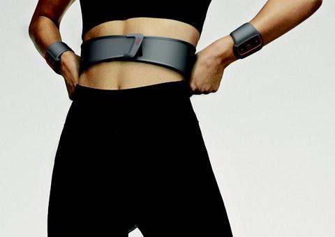 Foto einer sportlichen Frau, die einen Gürtel um die Taille und zwei Armbänder trägt, welche Vibrationssignale aussenden.