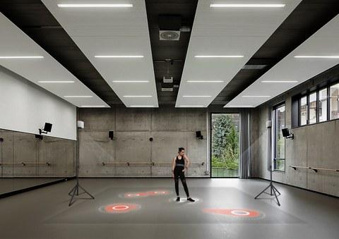 Foto: Eine Tänzerin steht in einem großen Raum, sie trägt einen Gürtel und Armbänder, die taktile Vibrationssignale aussenden. Auf den Boden werden mehrere rote Felder projiziert.