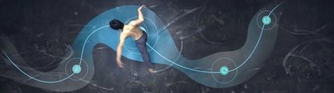 Foto: Man sieht einen Tänzer in Draufsicht. Eine Beamerprojektion zeigt auf dem Boden eine blaue Linie für den Weg des Tänzers und blaue Punkte und Symbole für die Interaktion mit anderen Tänzern. Der Tänzer befindet sich auf dem blauen Weg.