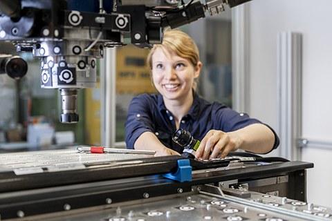 Das Foto zeigt eine junge Frau, die hinter einem Versuchsstand und installiert eine Kamera.