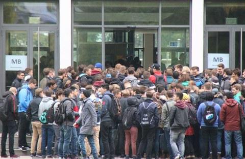 Das Foto zeigt viele Studierende von hinten. Eine große Traube steht vor einer Tür. Auf der Tür steht in Großbuchstaben MB für Maschinenbau. Das Foto zeigt die neuen Studierenden am Tag ihrer Einschreibung an der Fakultät Maschinenwesen der TU Dresden.