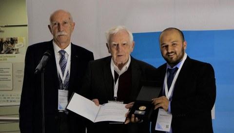Das Foto zeigt Prof. Heinz Linke, der die Fritz-Kesselring-Ehrenmedaille und eine Urkunde in den Händen hält. Neben ihm stehen zwei Männer.