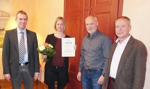 Auf dem Foto stehen vier Personen nebeneinander. Die zweite Person von links ist eine junge Frau. Lydia Hofmann hält in ihrer linken Hand eine Urkunde und in ihrer rechten Hand einen Blumenstrauß. Sie hat glatte, fast schulterlange blonde Haare.