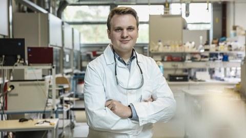 Das Foto zeigt Josua Viethen, der einen weißen Kittel trägt, die Arme vor der Brust verschränkt und in einem Labor steht.