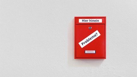 """Das Foto zeigt einen roten Briefkasten an einer weißen Wand. Auf dem Briefkasten steht """"Kummerkasten für Probleme in der Lehre""""."""