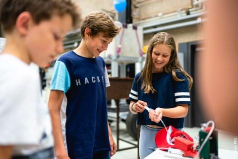 Das Foto zeigt drei Kinder, die zur Langen Nacht der Wissenschaft ein Experiment betrachten, das auf einem Tisch steht. Ein Mädchen hält einen transparenten Schlauch in der Hand, der zu dem Experiment hinführt.