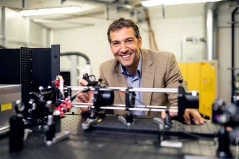Der internationale Laserexperte Prof. Andrés Lasagni steht hinter seinem Laser. Der Laser ist flach und steht auf einer Platte.