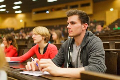 Das Foto zeigt Studierende im Hörsaal. Im rechten Bildvordergrund sieht man einen Student mit kurzen Haaren und grauer Jacke, die Arme stützt er auf dem Tisch ab. Neben ihm sitzt eine blonde Studentin mit rotem Shirt.