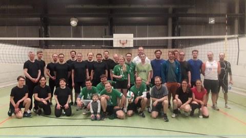 Auf dem Foto sieht man das Gruppenbild von Sportlern, die sich in einer Turnhalle vor einem Volleyballnetz in drei Reihen aufgestellt haben.