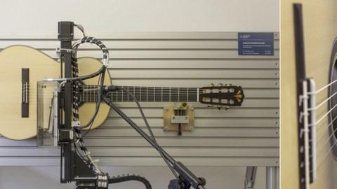 Das Foto ist zweigeteilt. Der überwiegende linke Teil zeigt eine Akustikgitarre, die in eine Wandvorrichtung gespannt ist. Der Anzupftest untersucht wie lange es dauert, bis ein Ton hörbar ist und wie lange der Ton hörbar bleibt. Der kleine rechte Teil des Fotos zeigt eine Detailaufnahme der Gitarrensaiten, die gerade von der Vorrichtung angezupft werden.