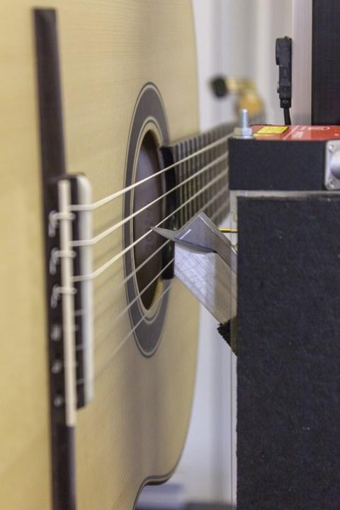 Detailaufnahme von Gitarrensaiten, die gerade von einer Testvorrichtung angezupft werden.